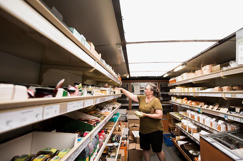 Nainen kokoaa ostoksia kauppa-auton sisällä.